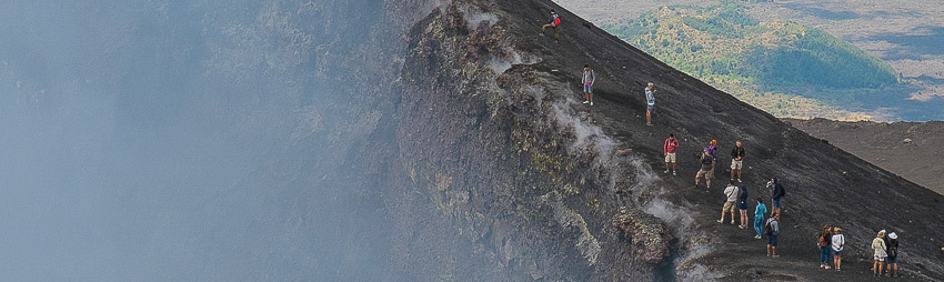 Tourists standing on the Etna crater rim